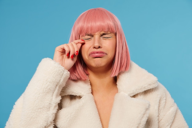 Unhappy young pretty pink haired female with bob haircut frowning her face while going to cry, keeping eyes closed and raisind hand to her face, standing