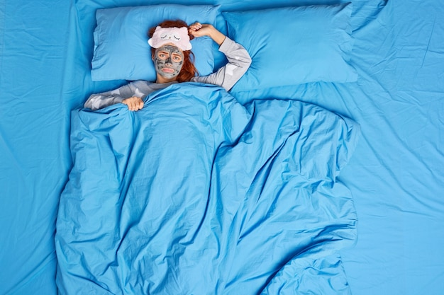 Unhappy young woman awakes in bad mood looks sadly, lying in bed under blue blanket wears nourishing beauty mask on face