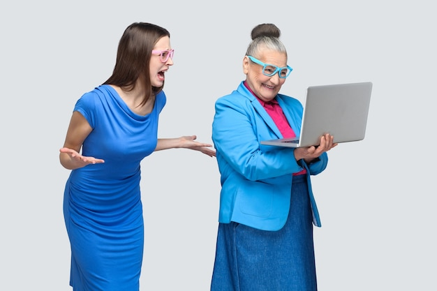 Unhappy young woman in blue dress shouting at aged woman working on laptop. relations or relationship on family between granddaughter and grandmother. indoor, studio shot, isolated on gray background