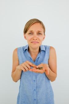 Несчастная молодая женщина, подсчитывая монеты на пальме