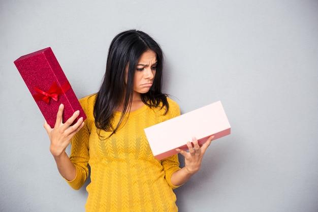 선물 상자를 들고 불행 한 젊은 여자