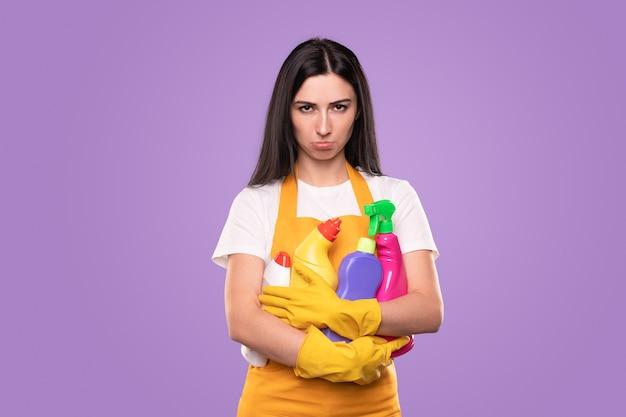 Несчастная молодая женщина в фартуке и перчатках держит кучу различных красочных бутылок с чистящими средствами во время повседневных домашних дел на фиолетовом фоне