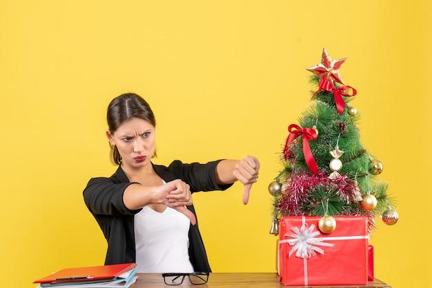 Несчастная молодая женщина в костюме делает негативный жест возле украшенной елки в офисе на желтом