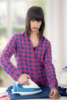 Unhappy young woman ironing clothes