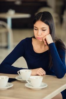 カフェに座っている不幸な若い女性