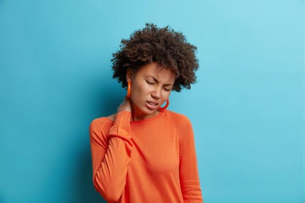 不幸な若い女性は痛みに苦しんでいます首は疲れたマッサージを感じます首は不快感を感じます目を閉じます青い壁の上に隔離されたカジュアルなオレンジ色のジャンパーを着ています