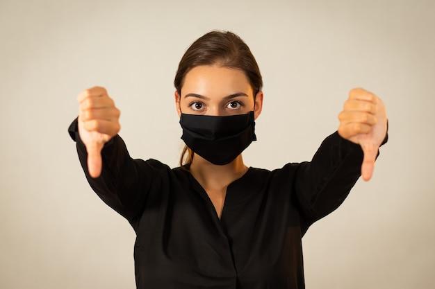 그녀의 부정적인 감정을 표현하는 검은 천 얼굴 마스크를 쓰고 불행한 젊은 여자