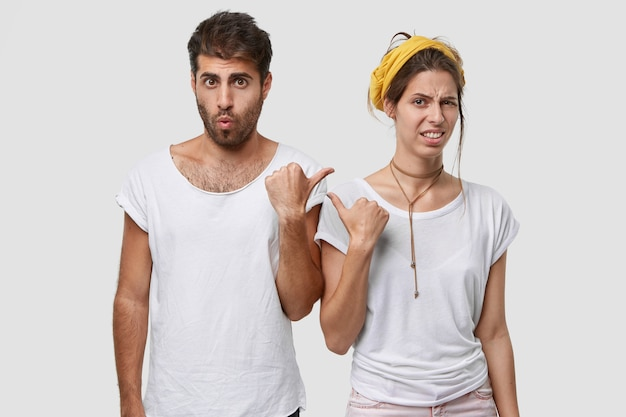 Unhappy young woman with european appearance, points with thumb at surprised guy, express dislike and surprisement, wear casual t shirts, isolated over white  wall