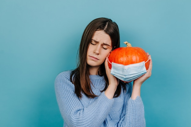 Unhappy young woman with eyes closed holds orange pumpkin in protective medical mask