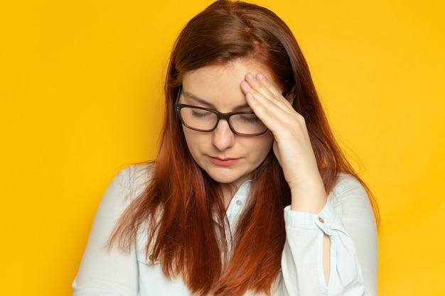 赤い長い髪と眼鏡の不幸な若い女性は頭痛に苦しんでいます