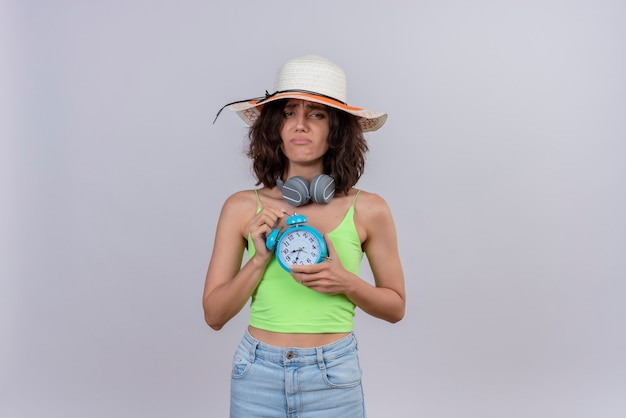 A unhappy young woman with short hair in green crop top wearing sun hat holding blue alarm clock on a white background