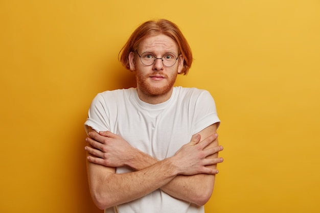 Unhappy youngster with bob hair, ginger beard, keeps hands crossed over body