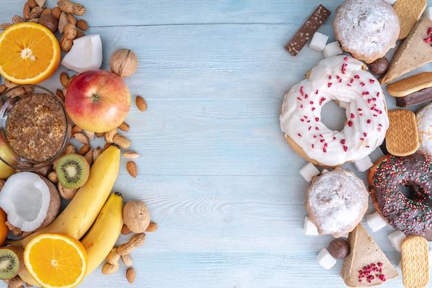 青い木製の背景に不健康で健康的なお菓子