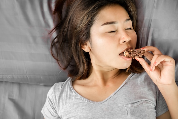 Unhealthy asian woman eating chocolate in bed
