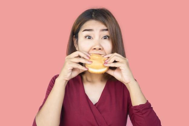Unhealthy asian woman over eating fast food hamburger
