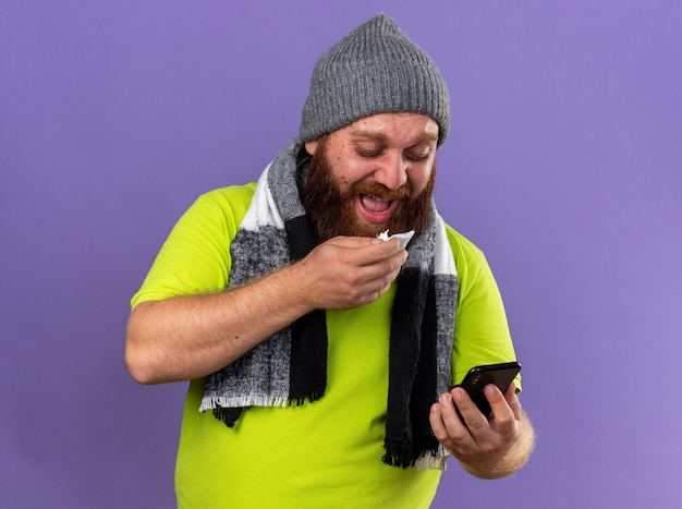 Unhealthy bearded man in hat and with warm scarf around neck feeling terrible suffering from flu looking at mobile phone going to sneeze standing over purple wall