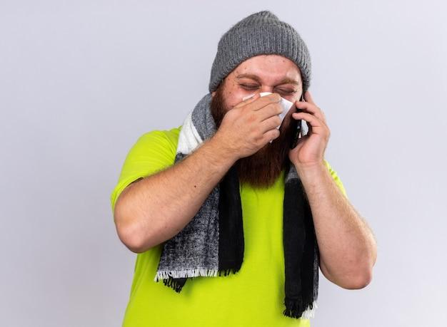 Uomo barbuto malsano in cappello e con sciarpa calda intorno al collo sensazione terribile sofferenza per l'influenza parlando al cellulare che soffia il naso che cola starnuti nel tessuto in piedi sul muro bianco