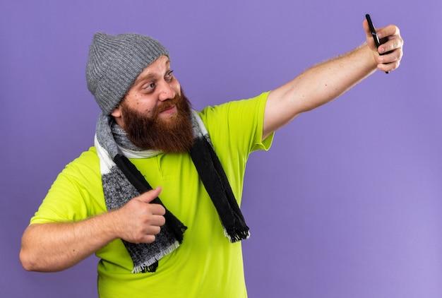Uomo barbuto malsano con cappello e sciarpa calda intorno al collo che sorride sentendosi meglio facendo selfie usando lo smartphone