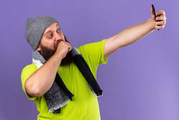 건강에 해로운 수염 난 남자 모자와 목 주위에 따뜻한 스카프가있는 기침은 보라색 벽 위에 서있는 스마트 폰을 사용하여 셀카를 더 잘하는 느낌