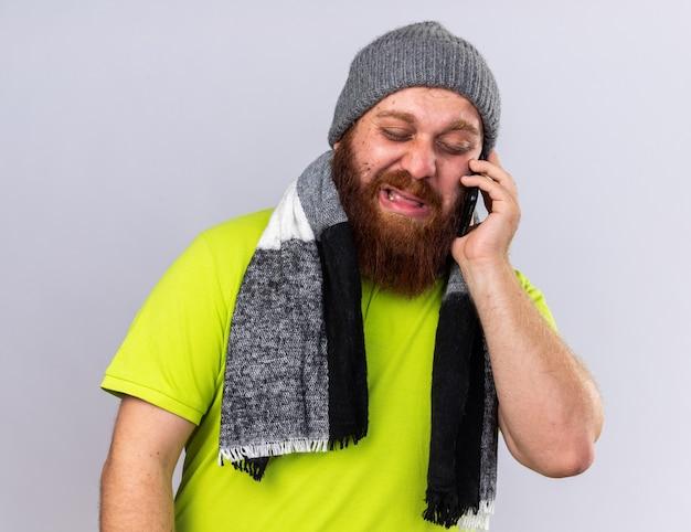 건강에 해로운 수염 난 남자 모자와 목 주위에 따뜻한 스카프로 독감으로 고통 받고 흰 벽 위에 서있는 슬픈 표정으로 혼란스러워 보이는 휴대 전화로 이야기