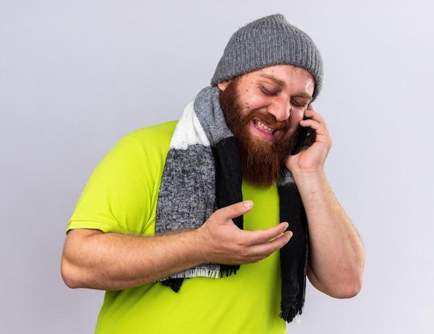 모자에 건강에 해로운 수염 난 남자와 목 주위에 따뜻한 스카프로 독감으로 고통 받고 흰 벽 위에 서있는 실망스러운 휴대 전화로 이야기
