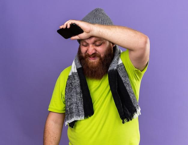 건강에 해로운 수염 난 남자 모자와 목 주위에 따뜻한 스카프로 보라색 벽 위에 서서 실망하고있는 휴대 전화를 들고 독감으로 끔찍한 느낌