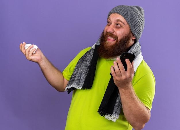 건강에 해로운 수염 난 남자 모자와 목 주위의 따뜻한 스카프로 끔찍한 느낌의 조직과 휴대 전화를 들고 보라색 벽에 서서 실망하는 독감