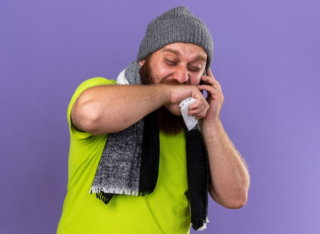 건강에 해로운 수염 난 남자 모자와 목 주위에 따뜻한 스카프로 보라색 벽 위에 서있는 조직에서 재채기를하는 휴대 전화를 불고 독감으로 고통받는 끔찍한 느낌