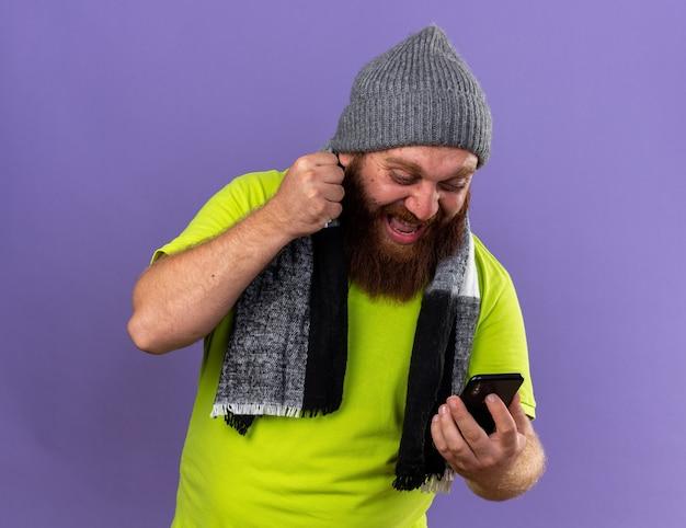 건강에 해로운 수염 난 남자 모자와 목 주위에 따뜻한 스카프로 독감으로 끔찍한 고통을 느끼며 휴대 전화가 보라색 벽 위에 서서 주먹을 움켜 쥐고 야생 소리를 지 릅니다.