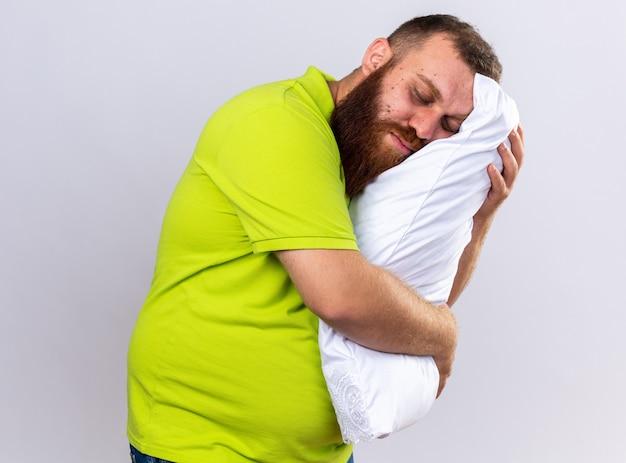 노란색 폴로 셔츠에 건강에 해로운 수염 난 남자가 아픈 베개를 들고 눈을 감고 자고 싶어합니다.