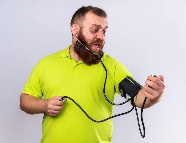 Нездоровый бородатый мужчина в желтой рубашке поло чувствует себя плохо, измеряя артериальное давление с помощью тонометра, выглядит обеспокоенным, стоя у белой стены