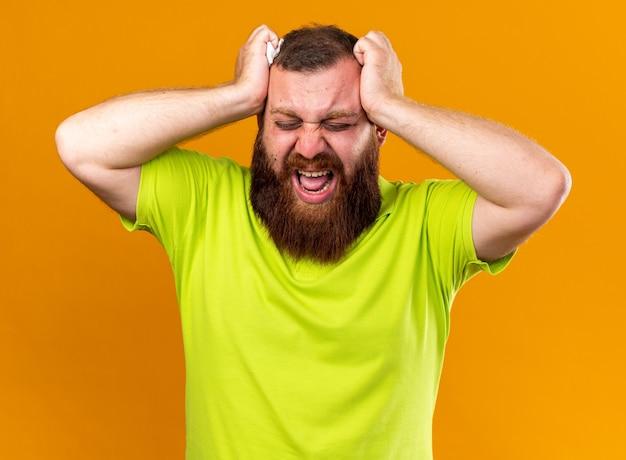 노란색 폴로 셔츠에 건강에 해로운 수염 난 남자는 실망한 표정으로 외치는 그의 머리를 만지는 추위와 강한 두통으로 끔찍한 고통을 느낍니다.