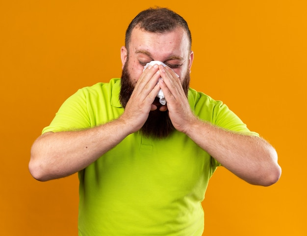 黄色いポロシャツを着た不健康なひげを生やした男は、オレンジ色の壁の上に立っているティッシュで鼻水をくしゃみをして冷たく吹いてひどいと感じている