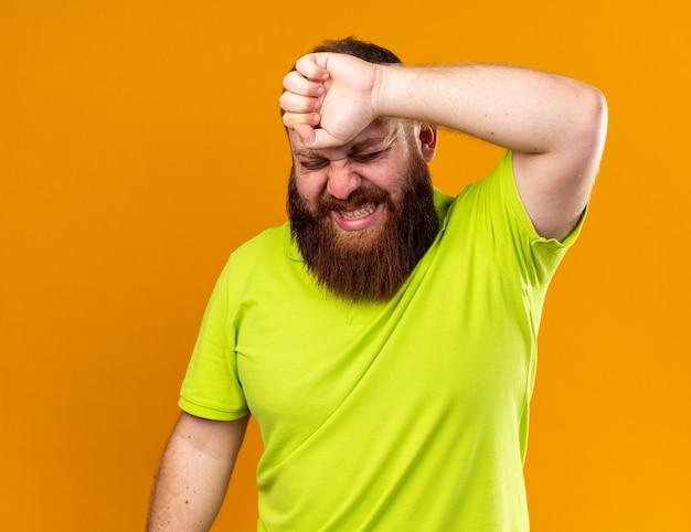 노란색 폴로 셔츠를 입은 건강에 해로운 수염을 가진 남자는 심한 두통을 느끼는 고통으로 고통받는 이마를 만져 추위로 고통받습니다.