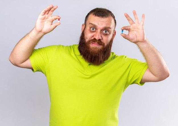 노란색 폴로 셔츠에 건강에 해로운 수염 난 남자가 다른 약을 들고 아픈 독감으로 고통받는 느낌