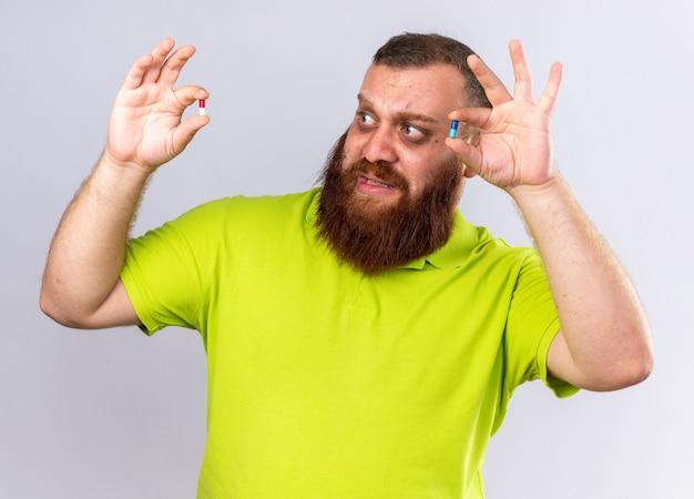 黄色のポロシャツを着た不健康なひげを生やした男性が、インフルエンザに苦しんで気分が悪くなり、混乱して怖がっているように見えるさまざまな錠剤を保持しています