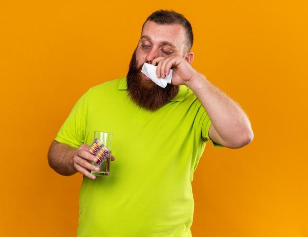 黄色いポロシャツを着た不健康なひげを生やした男が水と丸薬の入ったグラスを持っており、オレンジ色の壁の上に立つ寒さに苦しんでいるティッシュで鼻をくしゃみをしているのがひどい
