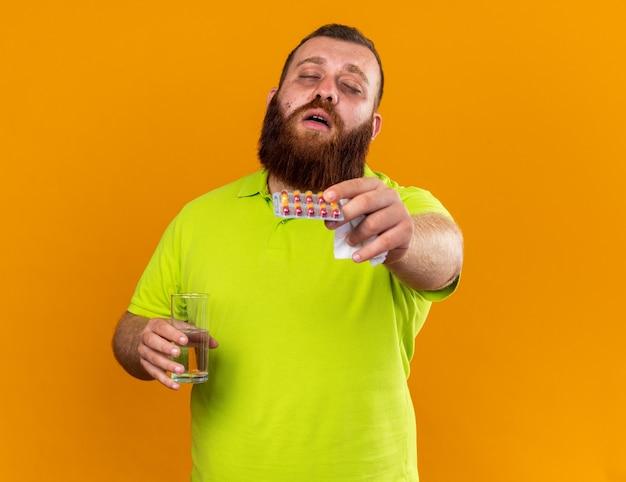 風邪や発熱の病気のウイルスに苦しんでひどい感じの水と丸薬のガラスを保持している黄色のポロシャツの不健康なひげを生やした男