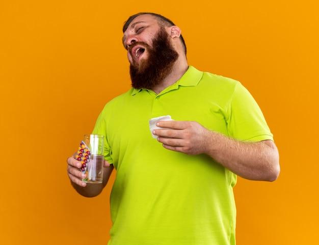 黄色いポロシャツを着た不健康なひげを生やした男が、オレンジ色の壁の上に立って、寒さに苦しんでひどいくしゃみをし、水と錠剤の入ったグラスを持っている