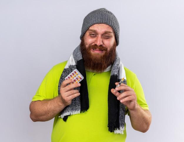 모자와 목 주위에 따뜻한 스카프가있는 건강에 해로운 수염 난 남자가 독감 들고 주사기와 알약으로 고통받는 아픈 느낌이 슬픈 표정으로 걱정됩니다.