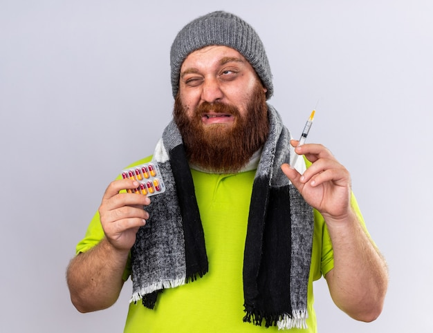 Unhealthy bearded man with hat and warm scarf around neck feeling sick suffering from flu holding syringe and pills looking worried making grimace with disgusted expression on white wall