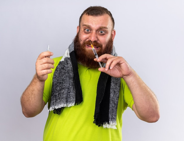 목 주위에 따뜻한 스카프로 건강에 해로운 수염을 가진 남자가 독감 들고 주사기와 앰플을 앓고 걱정하고 무서워하는 고통을 느낍니다.