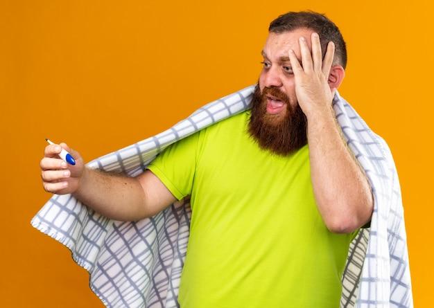 Uomo barbuto malsano avvolto in una coperta che si sente male soffre di freddo che controlla la temperatura usando il termometro essendo preoccupato e spaventato