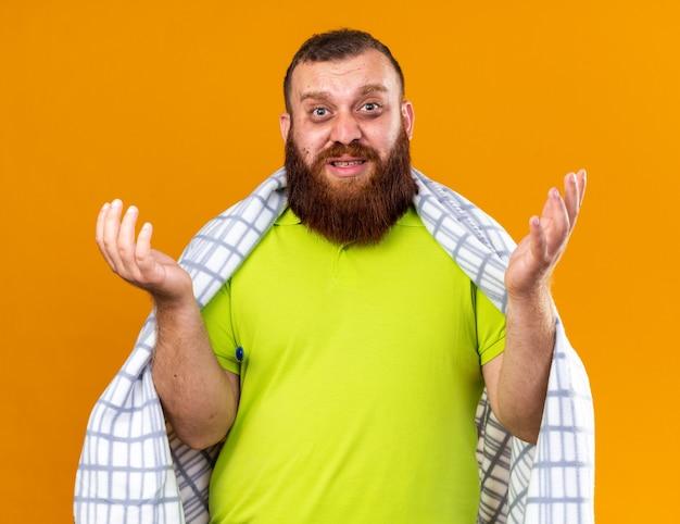 Uomo barbuto malsano avvolto in una coperta che si sente male soffre di freddo che controlla la temperatura usando un termometro che sembra confuso con le braccia alzate