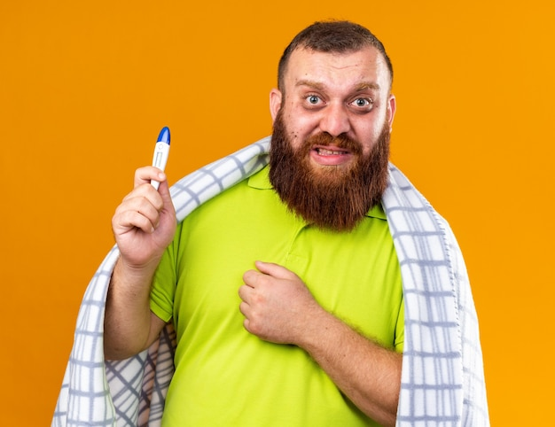 Uomo barbuto malsano avvolto in una coperta che si sente male soffre di freddo che controlla la temperatura usando un termometro che sembra preoccupato e confuso in piedi sul muro arancione