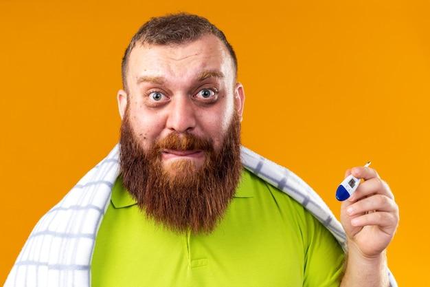 Uomo barbuto malsano avvolto in una coperta che si sente male soffre di freddo che controlla la temperatura usando un termometro che sembra preoccupato e spaventato in piedi sul muro arancione