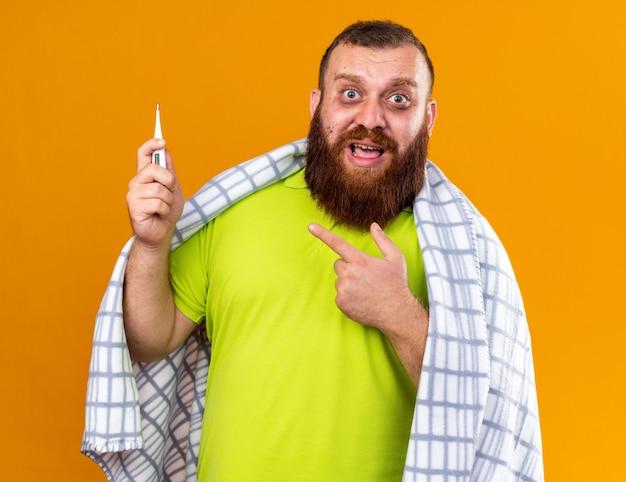 Uomo barbuto malsano avvolto in una coperta che si sente male soffre di freddo che controlla la temperatura usando un termometro che sembra preoccupato in piedi sul muro arancione