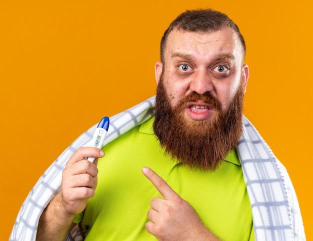 Uomo barbuto malsano avvolto in una coperta che si sente male soffre di freddo controllando la temperatura usando il termometro che punta con il dito indice preoccupato in piedi sul muro arancione