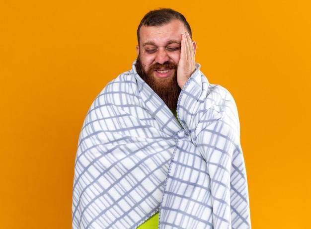Uomo barbuto malsano avvolto in una coperta che si sente male, soffre di febbre fredda e forte mal di testa