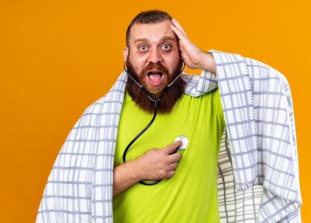 Uomo barbuto malsano avvolto in una coperta che si sente male soffre di freddo ascoltando il suo battito cardiaco usando lo stetoscopio spaventato